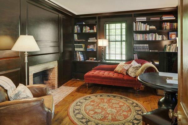 Prachtig dat groenzwart op de muur in contrast met de ingetogen rode bank en het kleed. Ik wil ook een open haard!