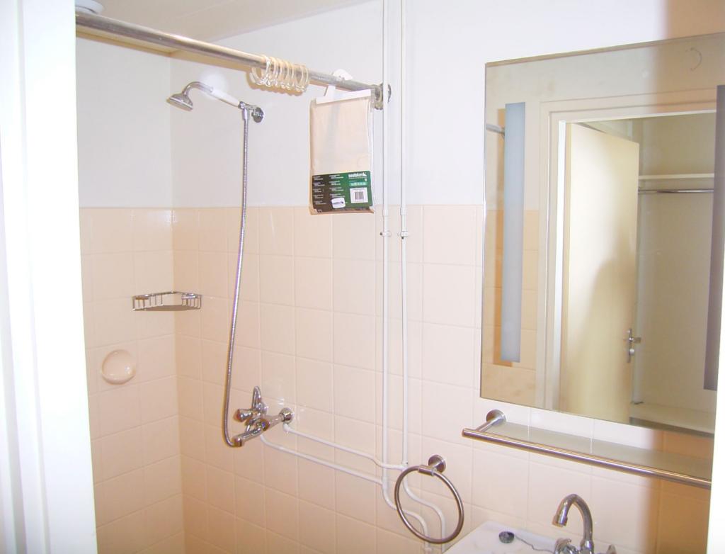 foto van onuitgepakt douchegrodijn, een randje wastafel, een betegelde muur en de schaduw van de makelaar zelf: Van der Reijden Makelaardij